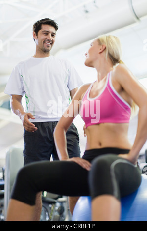 Smiling couple talking in gym - Stock Photo