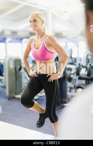 Smiling woman working out in gym - Stock Photo