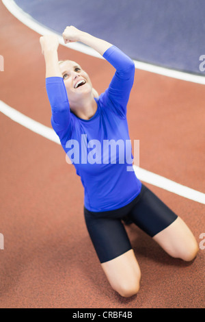 Woman shouting on indoor track in gym - Stock Photo