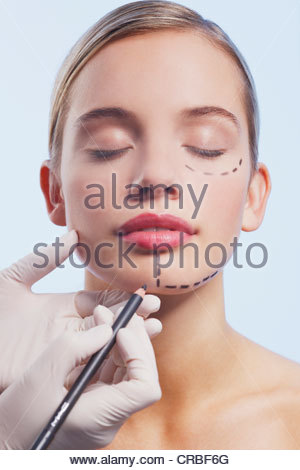 Close up of woman's face being marked with dotted lines - Stock Photo