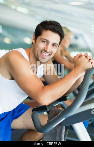 Man using exercise machine in gym - Stock Photo