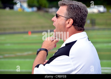 Coach shouts instruction from the sideline at a high school football game in Maryland - Stock Photo