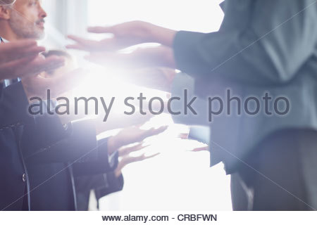 Business people standing face to face in a row with palms up - Stock Photo