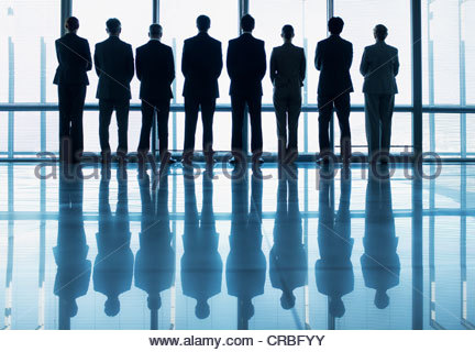 Silhouette of business people in a row looking out lobby window - Stock Photo
