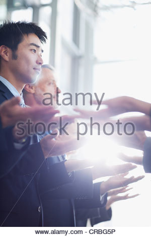 Business people standing in row with palms up - Stock Photo