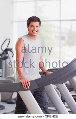 Portrait of smiling man walking on treadmill in gymnasium - Stock Photo