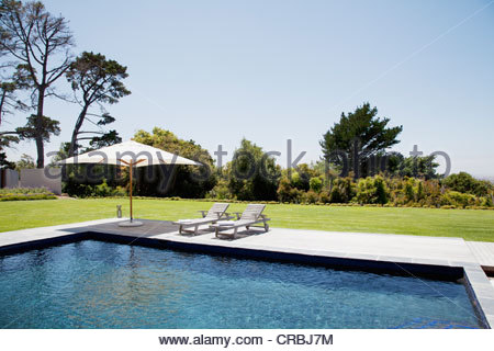 Swimming pool, lounge chairs and umbrella - Stock Photo