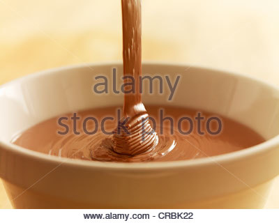 Close up of chocolate syrup pouring into bowl - Stock Photo