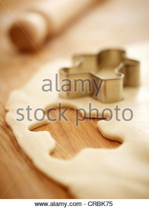 Gingerbread man cookie cutter on dough - Stock Photo