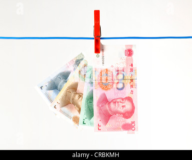 Fan of Chinese yuan or renminbi banknotes, the currency of the People's Republic of China, hanging on a clothesline, - Stock Photo