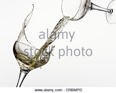 White wine pouring from one glass into another - Stock Photo