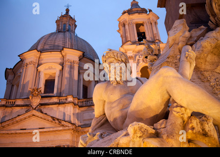 Statue of the Fontana dei Quattro Fiumi or Fountain of the Four Rivers and the church of Sant'Agnese in Agone at - Stock Photo