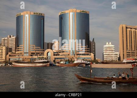 Twin Towers and traditional abra boats on Dubai Creek in Dubai, United Arab Emirates, Middle East, Asia - Stock Photo