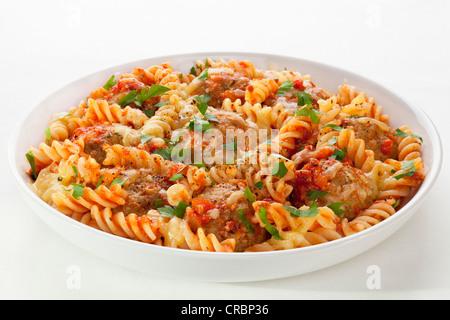 Fusili pasta baked with meatballs and marinara, topped with melting mozzarella. - Stock Photo