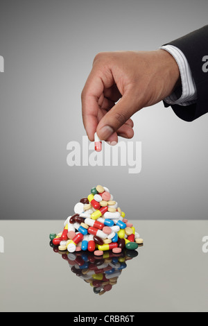 Businessman stacking pills on counter - Stock Photo