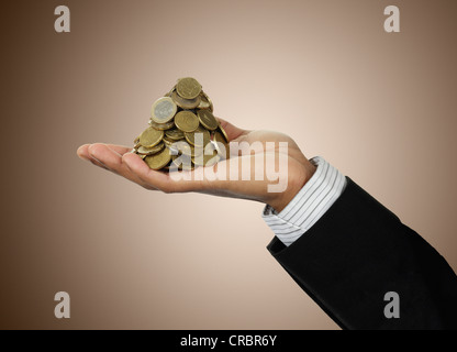 Businessman holding stack of Euro coins - Stock Photo