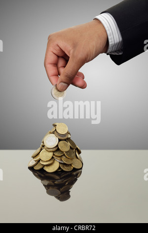 Businessman stacking Euro coins - Stock Photo