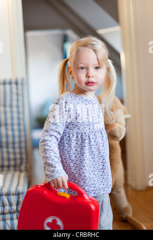 Girl carrying toy first aid kit - Stock Photo