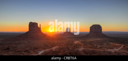 Sunrise behind mesas, West Mitten Butte, East Mitten Butte, Merrick Butte, Scenic Drive, Monument Valley, Navajo - Stock Photo