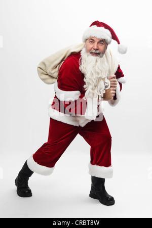 Santa carrying sack of Christmas gifts