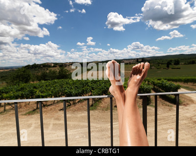 Woman resting feet on railing outdoors - Stock Photo