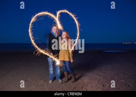 Couple playing with sparklers on beach - Stock Photo