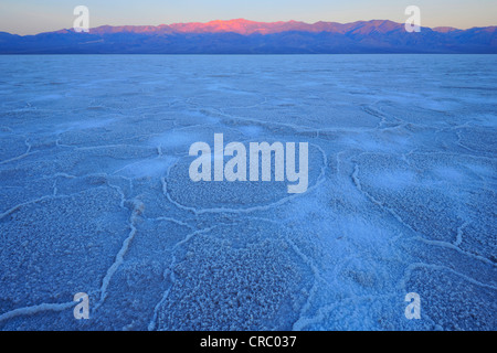 Salt pan, salt crystals, sunrise in Badwater Basin above Panamint Range, Death Valley National Park, Mojave Desert, - Stock Photo