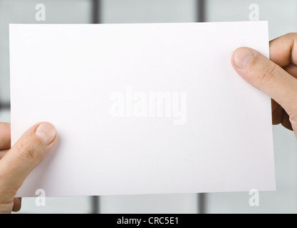 White blank sheet of paper in hands - Stock Photo