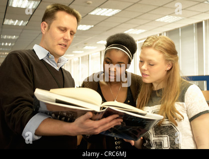 Students reading with teacher in library - Stock Photo