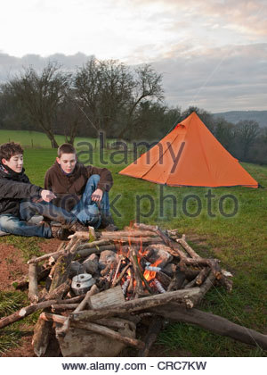 Boys sitting by campfire in meadow - Stock Photo