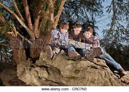 Boys reading map on rock formations - Stock Photo