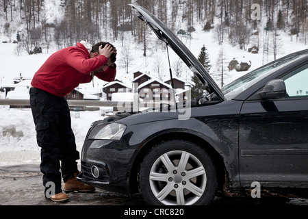 Frustrated man checking car engine - Stock Photo