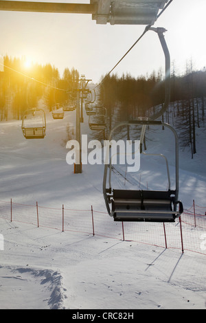 Ski chairlift over snowy landscape - Stock Photo