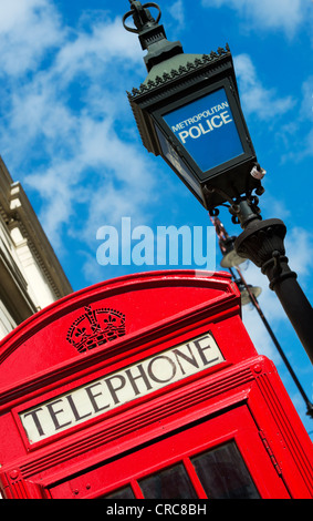Metropolitan Police light and red telephone box against blue sky. London, England - Stock Photo