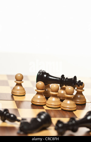 White pawns surrounding black chess king - Stock Photo
