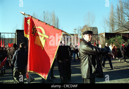 Berlin, an activist of the MLPD with red flag - Stock Photo