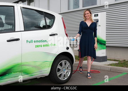 Woman holding a charging plug for a Suzuki Splash electric car, in front of a Charge CP700A charging point from - Stock Photo