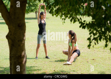 Two beautiful women stretching in city park after running and sport activity - Stock Photo