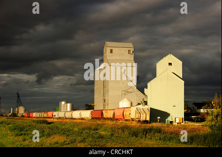 Typical granary with train and storm clouds, Manitoba, Canada - Stock Photo