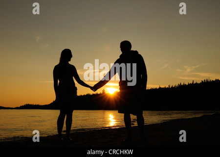 Couple holding hands on the shores of Lake Superior at sunset, Ontario, Canada - Stock Photo