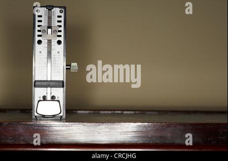 Metronome standing on a piano - Stock Photo