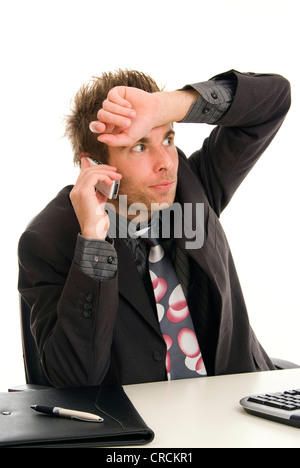 stressed young businessman in his office, phoning with his mobile, with his hand on his forehead - Stock Photo