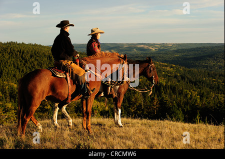 Cowboy and cowgirl sitting on horseback, looking into the distance, Saskatchewan, Canada, North America - Stock Photo