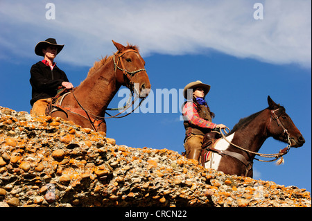 Cowboy and cowgirl on horses looking into the distance, Saskatchewan, Canada, North America Stock Photo