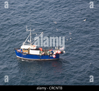 Orkney Fishermen lifting lobster pots from small fishing boat Stock Photo