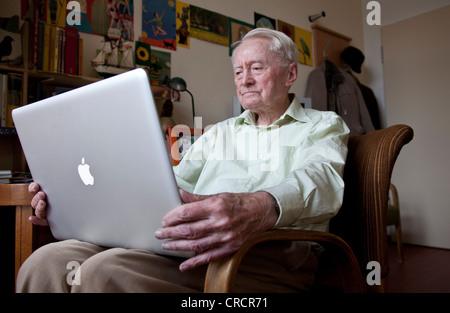 Elderly man, senior citizen holding an Apple Macintosh laptop computer on his knees, nursing home, retirement home, - Stock Photo