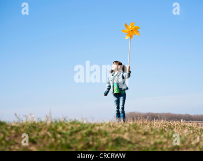 Girl standing in meadow with toy windmill - Stock Photo