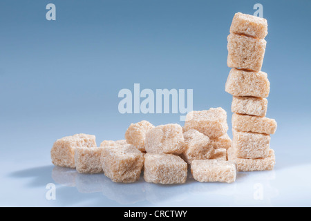 Vertical stack of brown sugar cubes on blue. Horizontal. - Stock Photo