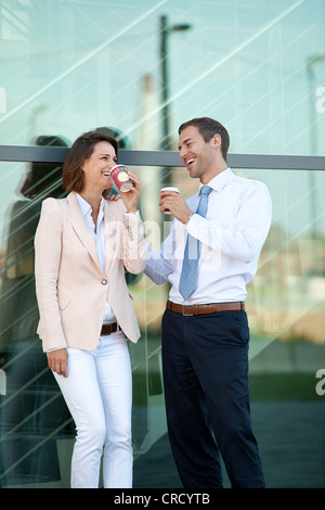 Businessman and businesswoman with coffee to go talking - Stock Photo
