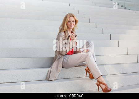 Blond woman having a snack on stairs - Stock Photo